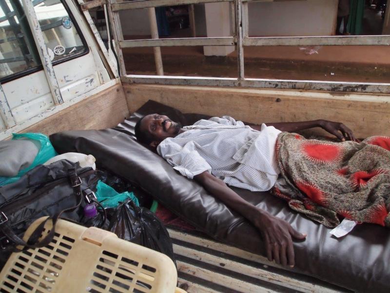 De vader van Kaloli wordt gebracht met de ugandese 'ambulance'.