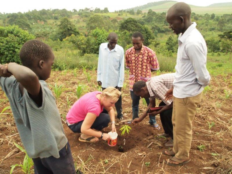 Joanne plant een mango boom op het land waar gebouwd gaat worden aan Paul's (rode shirt) school.